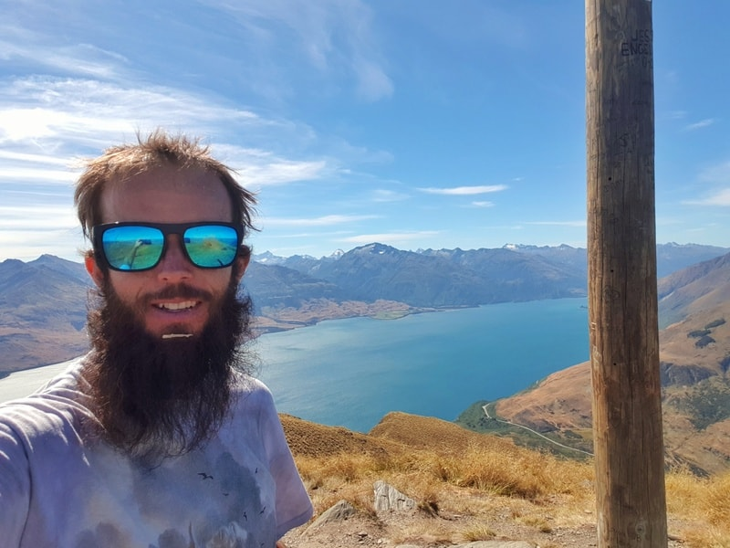 a selfie I took from the summit of Isthmus Peak Track. You can see Lake Wanaka in the background and I seem to have some banana in my beard.