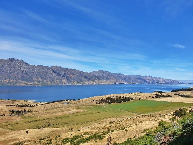 a view of lake hawea surrounded by fields