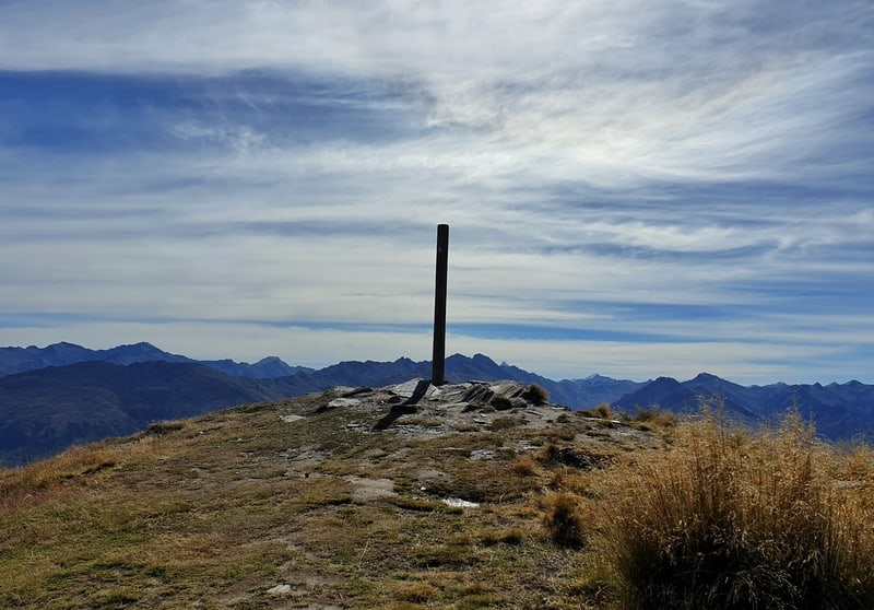 a pole in the ground marking the summit of isthmus peak with clouds in the background